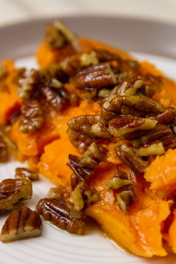 half od a sweet potato with pecan sauce on top