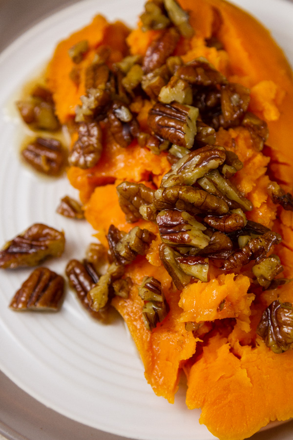 half of a baked sweet potato covered with pecans