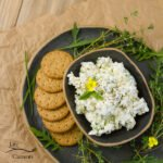 Top down or flatlay looking down on feta cheese spread served on a dark platter with crackers and lost of fresh herbs