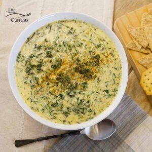 looking down on a big white bowl filled with spinach and artichoke soup and a spoon next to it with some crackers