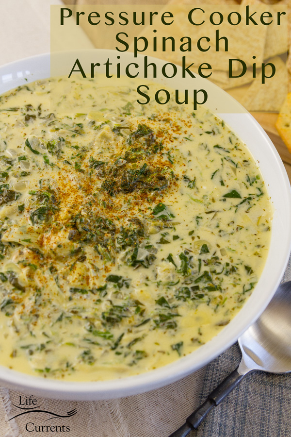 Spinach and artichoke creamy soup in a white bowl and a spoon on the side