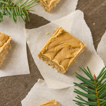 pieces of brown sugar fudge on pieces of parchment paper with fir branches