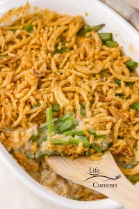 Green bean casserole in the casserole dish being served with a wooden spoon