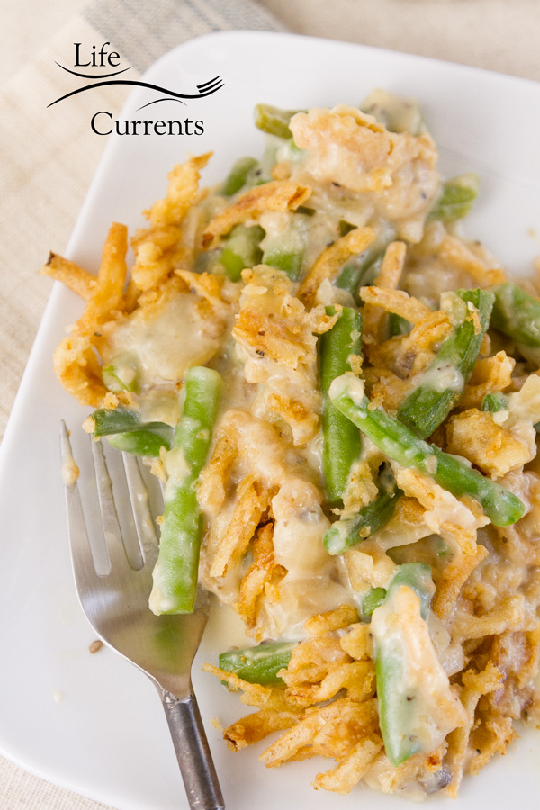 A serving of Green Bean Casserole on a white plate with a fork