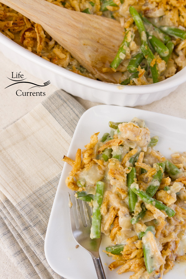 Green bean casserole in a white casserole dish with a wooden serving spoon and a serving on a white plate