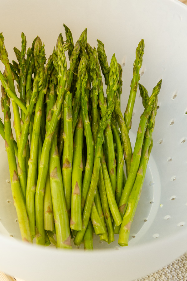 asparagus being cleaned in a white colander