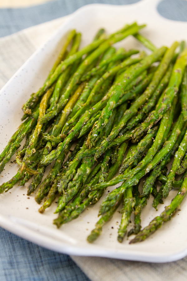 roasted asparagus on a white platter