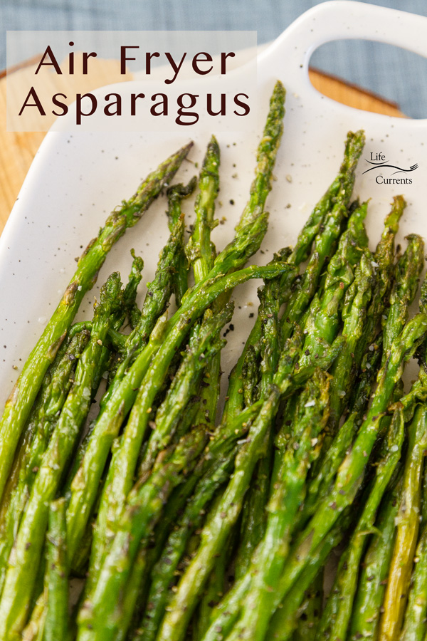 asparagus roasted in the air fryer and served on a white platter with a wood block and a blue napkin in the back
