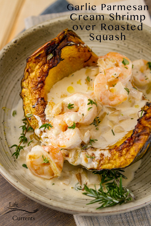 cooked shrimp in garlic sauce poured over roasted squash wedges with fresh herbs around it