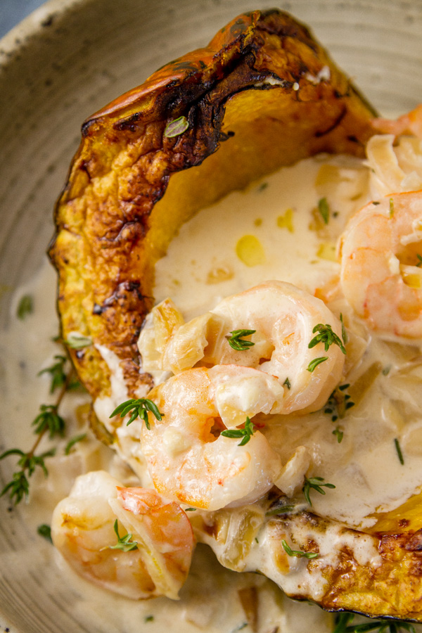 cooked shrimp in garlic parmesan cream sauce over a wedge of roasted squash