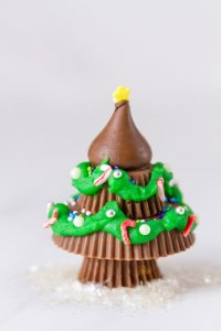 one christmas tree made from peanut butter cups and a hershey's kiss decorated with icing and sprinkles on a white background