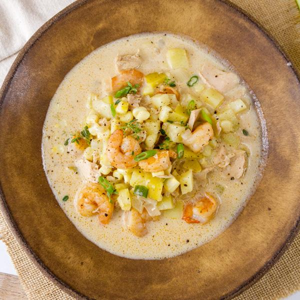 A brown bowl filled with Cajun seaffod chowder - shrimp, corn, potatoes, tuna