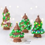 square crop of 4 peanut butter cup Christmas trees with twinkle lights in background