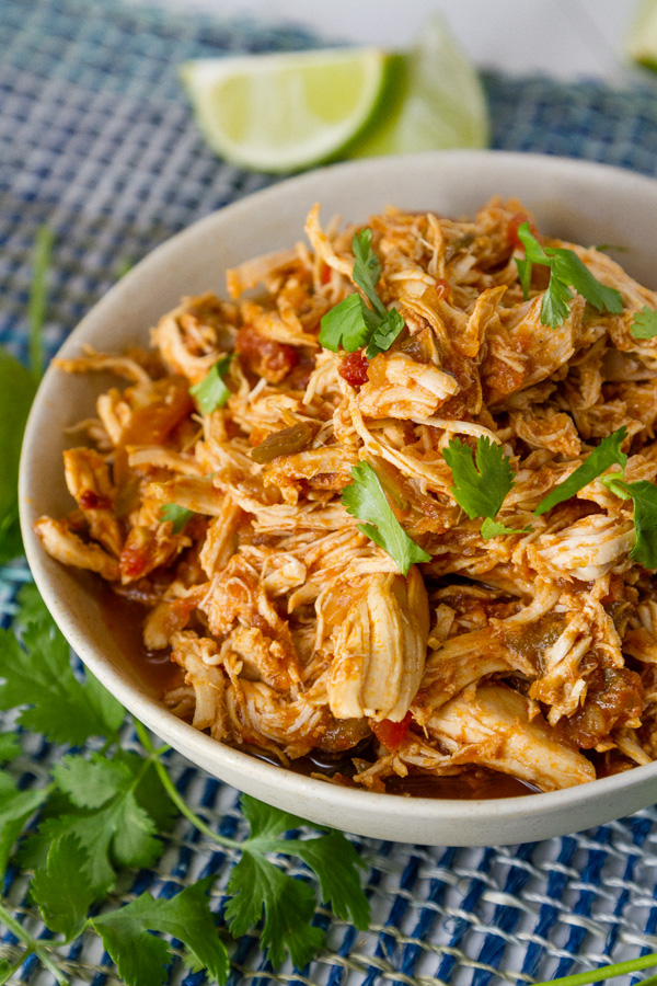 a bowl full of shredded cooked chicken with lime wedges and cilantro