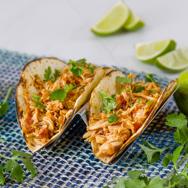 square crop of two chicken tacos with guacamole
