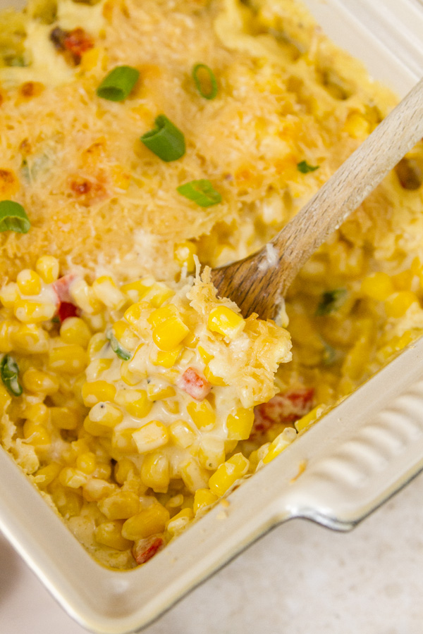 Corn side dish in a servings dish with a wooden spoon
