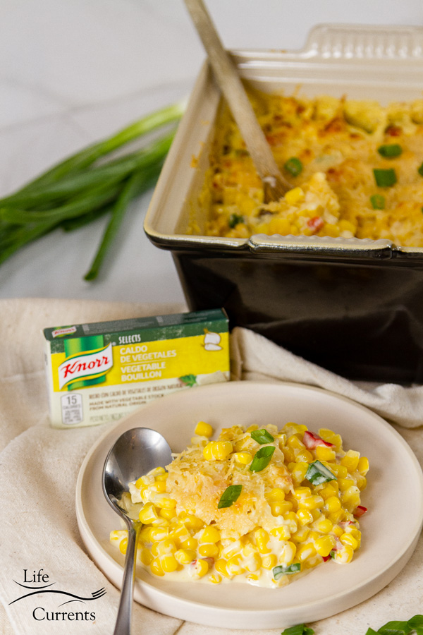 a serving of creamed corn on a plate with a box of Knorr and the creamed corn in the background with some green onions
