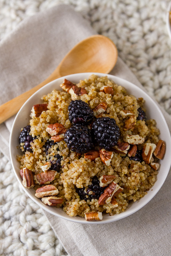 top down on a bowl of Breakfast Quinoa Bowl with Blackberries with a wooden spoon on a white cloth background
