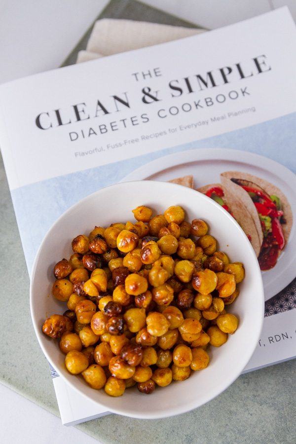 Buffalo Roasted Chickpeas in a white bowl on the book The Clean & Simple Diabetes Cookbook