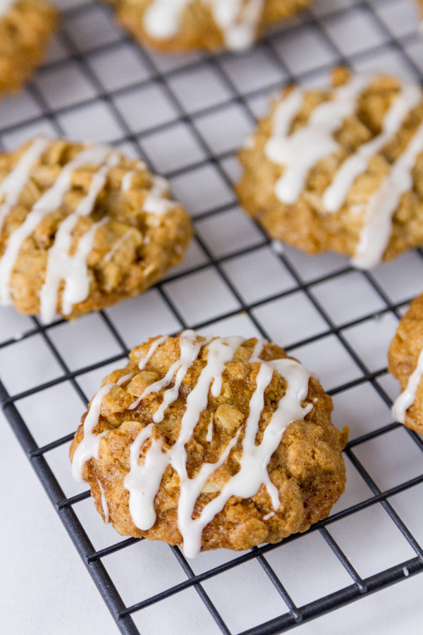 Eggnog Oatmeal cookies with icing on a cooling rack