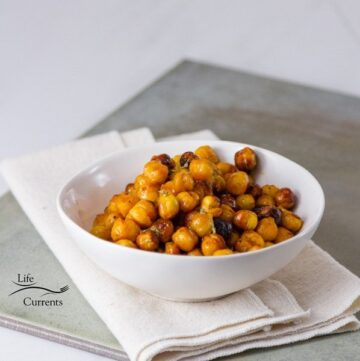 Square crop of Buffalo Roasted Chickpeas in a white bowl on a grey background