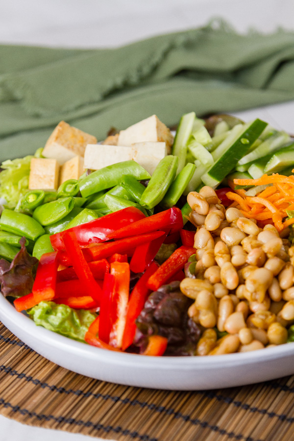 Asian Fusion Bowl with beans, greens, veggies in a white bowl on a mat with a green napkin