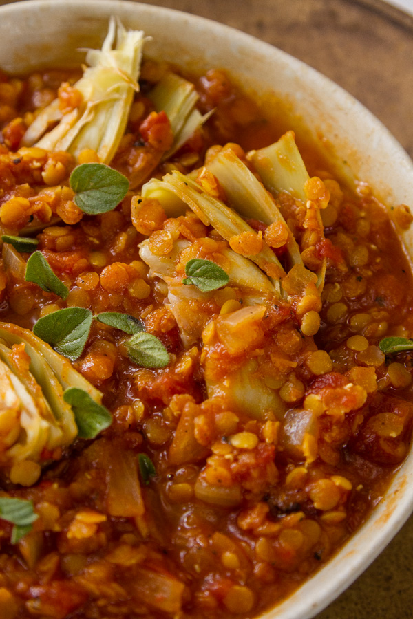 Red Lentil and Artichoke Stew in a tan bowl, close up