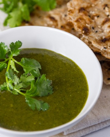 Tamarind Cashew Dipping Sauce in a white bowl with sangak bread and cilantro in the background