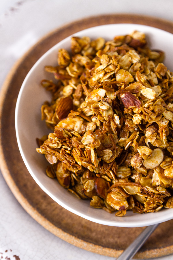 Homemade Granola Recipe served in a white bowl on a brown plate with a spoon on the right