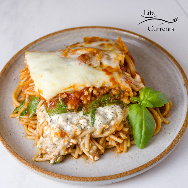 Spinach Provolone Baked Pasta on a plate with a garnish of fresh basil