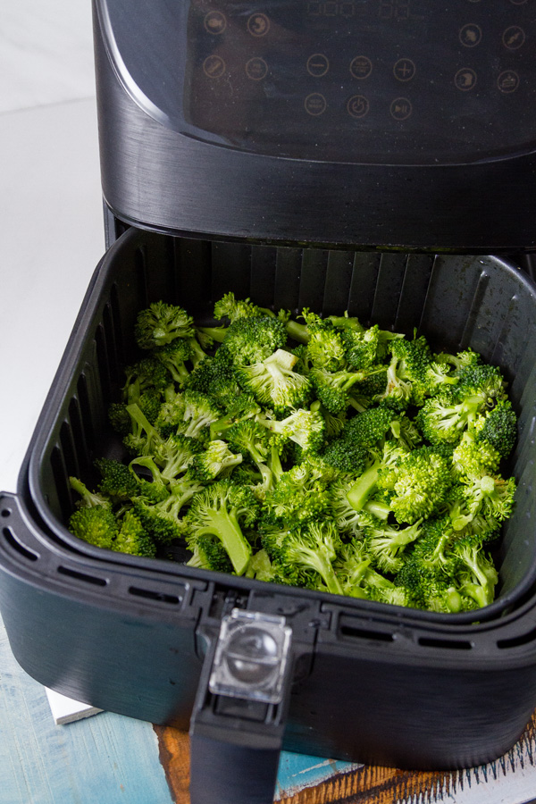 broccoli in the basket of the air fryer ready to cook for Air Fryer Roasted Broccoli