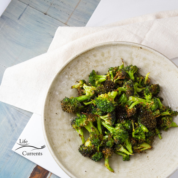 square crop top down of Air Fryer Roasted Broccoli in a white bowl on a white cloth with a blue counter top
