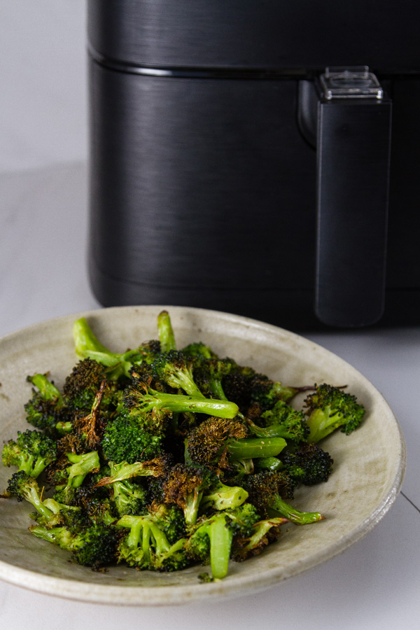 Air Fryer Roasted Broccoli in a bowl in front of the air fryer