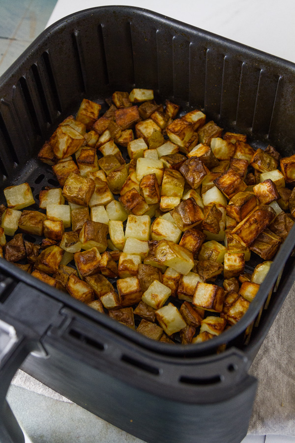 Potatoes cooked in the air fryer crispy and still in the basket