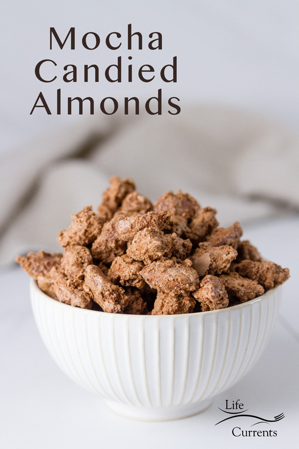 Mocha Candied Almonds in a white bowl on a white background with a grey napkin in the back