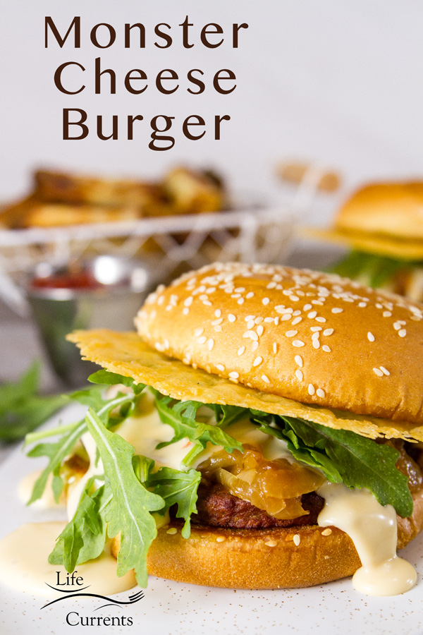 A close up of the Monster Cheese Burger with another burger and fries with ketchup in the background, title on the upper left