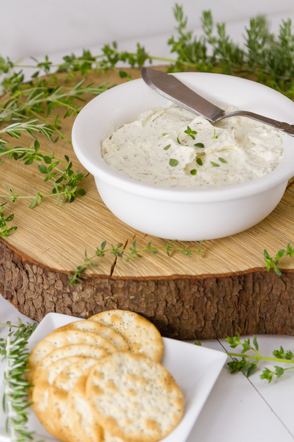 Garlic and Herb Cheese Spread in a white bowl with a knife and some crackers in the lower left
