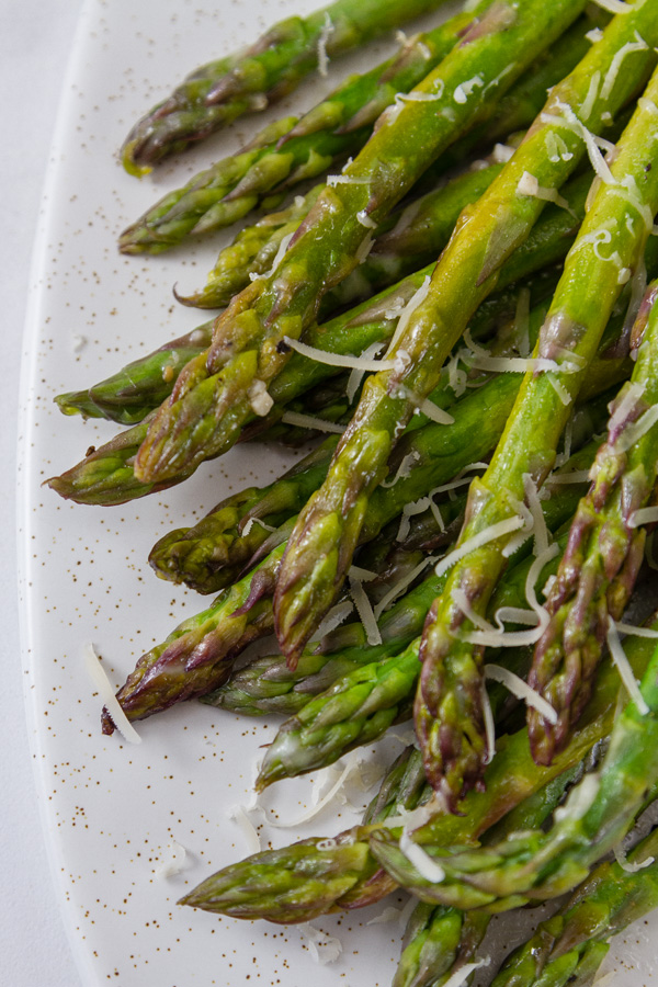 grilled asparagus arranged on a white platter topped with Parmesan