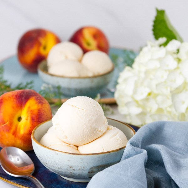square crop of two bowls of Peach ice cream with peaches and flowers aoround them