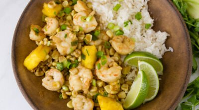 square crop of Foil Packet Caribbean Shrimp with coconut rice and lime wedges in a brown bowl