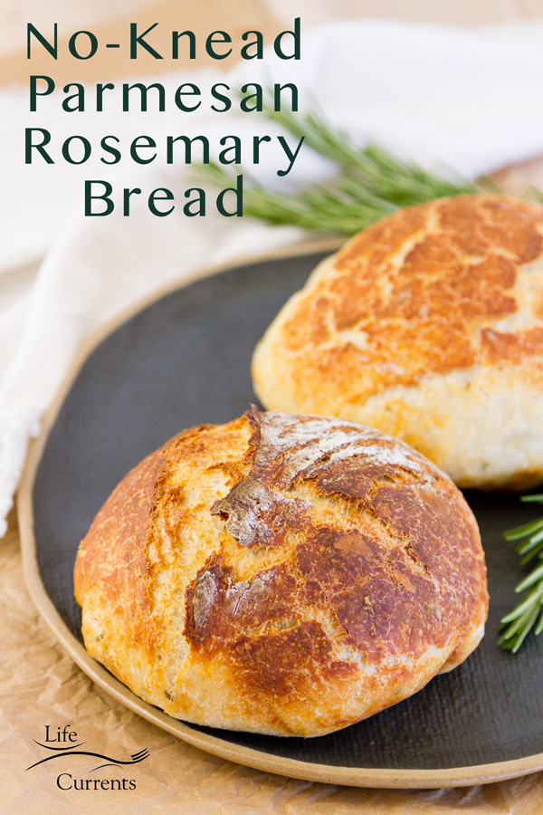 two loaves of No-Knead Parmesan Rosemary Bread on a drk platter with a white cloth and fresh roasmary around