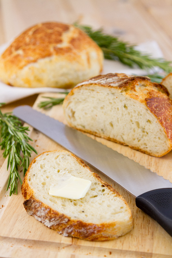 a slice of No-Knead Parmesan Rosemary Bread with butter on top, a bread knife next to it, and the rest of the loaf in the back. There's rosemary and another loaf in the background