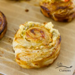 square crop of one Pepper Jelly Cream Cheese Pinwheel with logo at the bottom