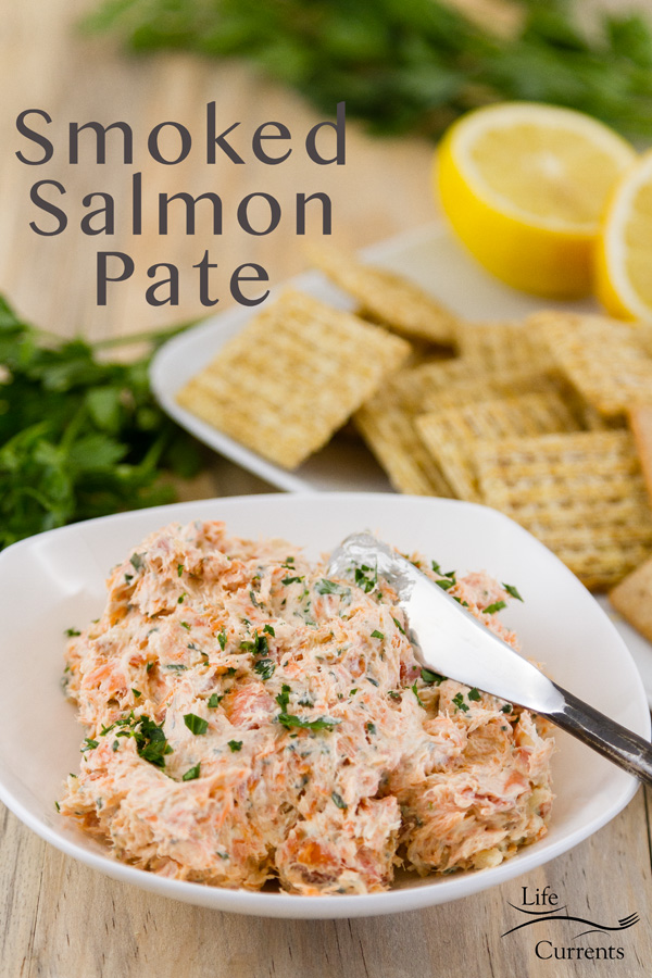 Title on image: Smoked Salmon Pate with the spread in a white dish with a knife served with crackers, lemons, and fresh parsley