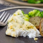 a piece of baked Pacific halibut served with potatoes and broccoli