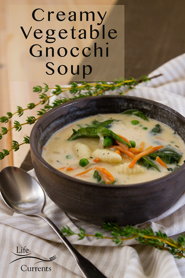 Creamy Vegetable Gnocchi Soup in a dark bowl with a spoon on a white striped cloth with fresh thyme. Title on image