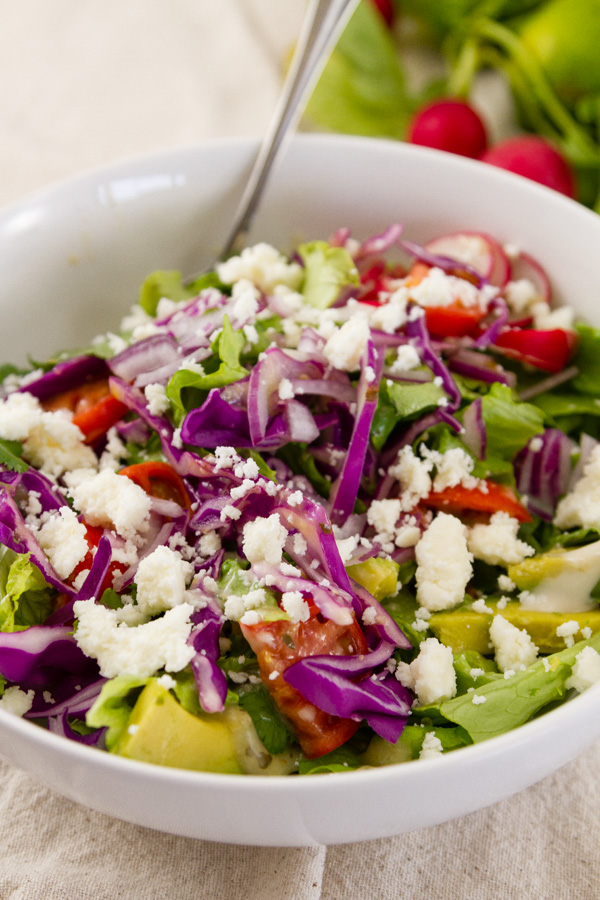 fresh salad bowl with lettuce, tomatoes, avocado, purple cabbage, red onions, and queso fresco.