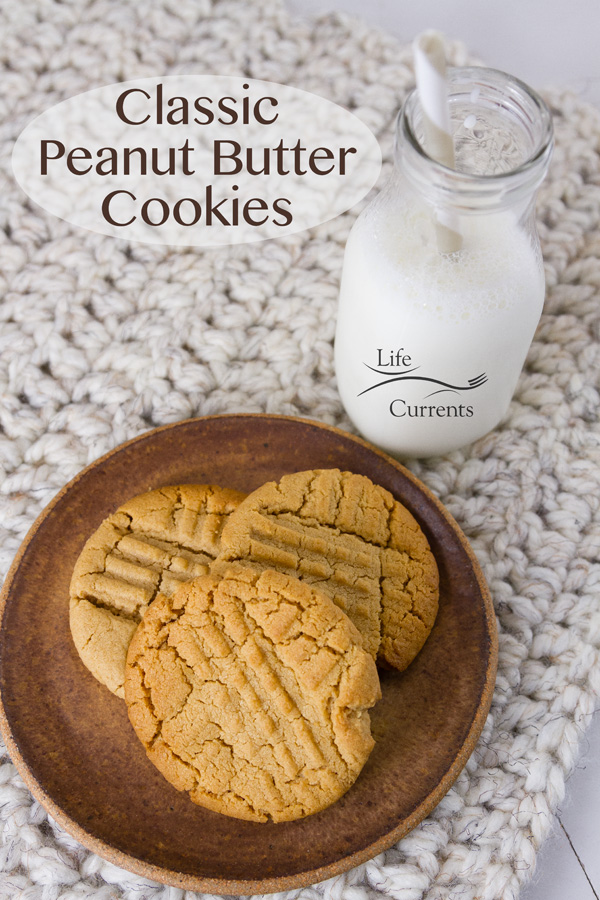 Classic Peanut Butter Cookies on a brown plate with a glass of milk, title on image