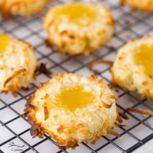 square crop of thumbprint cookies filled with lemon curd on a wire rack
