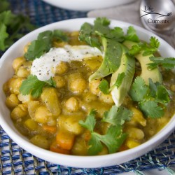 Vegetarian Chili Verde Stew in a white bowlwith avocado, sour cream, and cilantro
